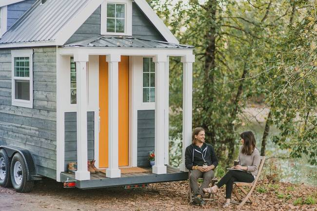 The Heirloom Tiny Home has a columned front porch and a striking orange door