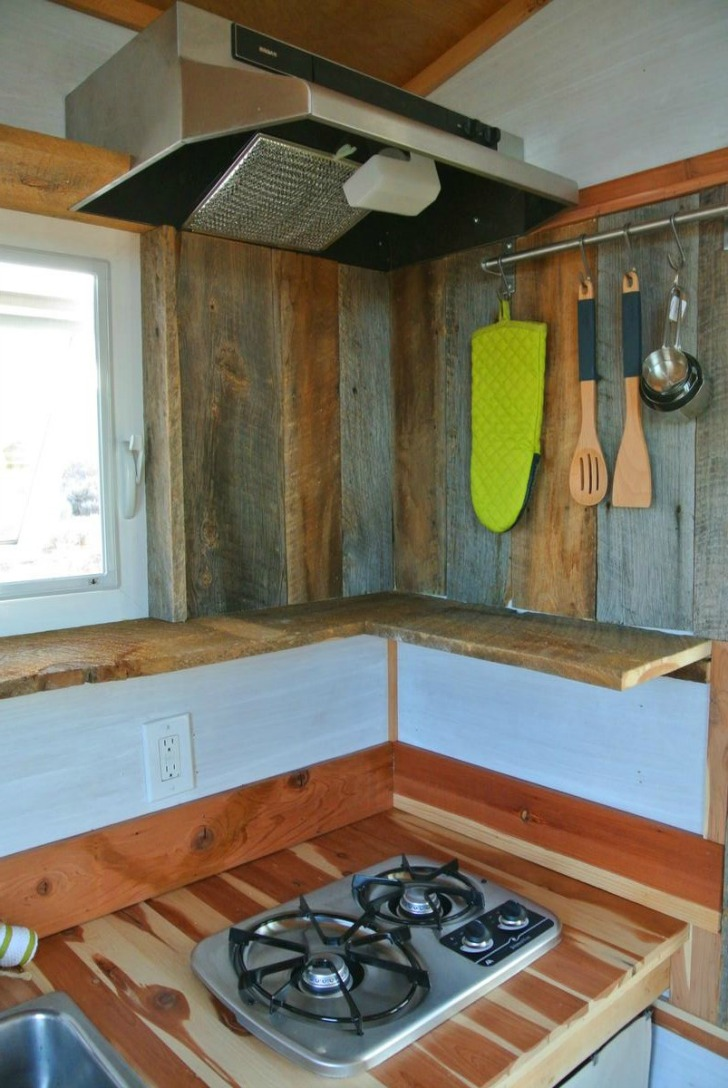 Tiny house has modern wood paneling in tiny kitchen